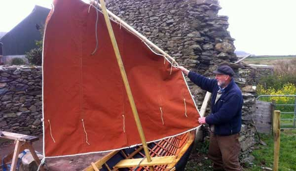 Danny Sheehy checking for holes in the sail of a naomhóg